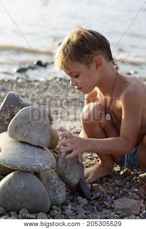 Сhild playing on pebble beach of the Sea of Azov