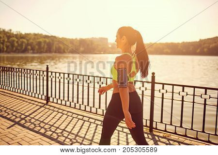 A sporty girl is walking in a sporting walk in the park by the lake.