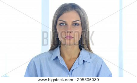 Serious Young Woman Looking At Camera In Office