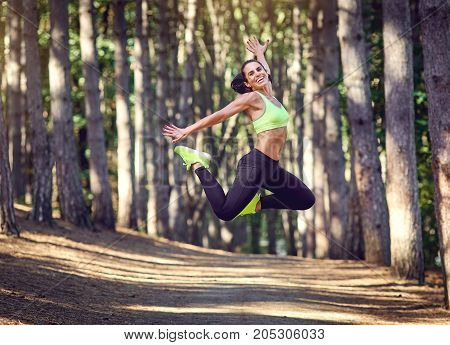 Sports girl brunette jumped in nature. A jumping young woman in a forest.