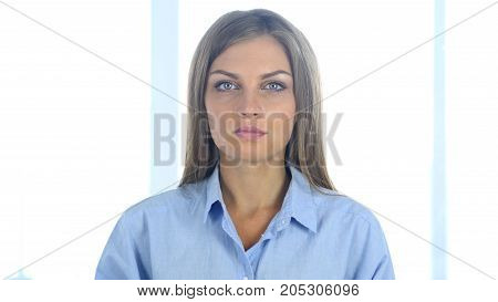 Beautiful Woman Sitting In Office, Looking At Camera