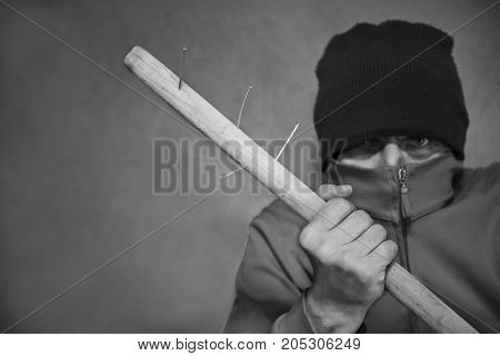 Man with covered face holding a wooden stick with nails head and shoulders studio portrait. In black and white