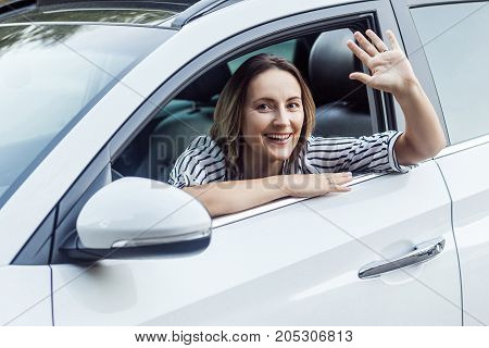 Well Hi! Happiness Business Woman In A Car, Looking At Camera And Send Hello Sign.