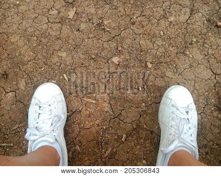 Dirty Cracked Soil Background with sneakers in closeup