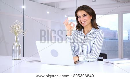 Satisfied Young Woman Gesturing  Okay Sign At Work