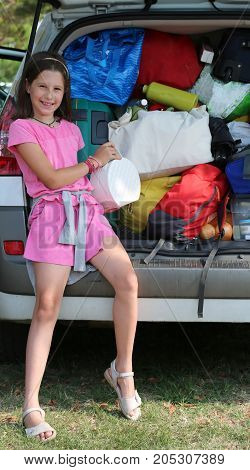 Little Girl Loads Her Purse In The Car Trunk