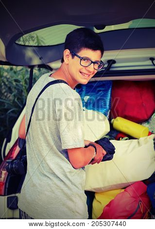 Smiling Young Boy With Glasses Puts Suitcases In The Luggage Wit