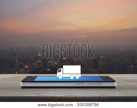 Truck flat icon on modern smart phone screen on wooden table over blur of cityscape on warm light sundown Business transportation service concept