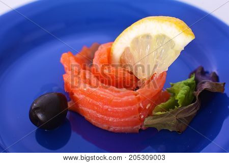 Slice of salmon with lemons and olives on a plate.