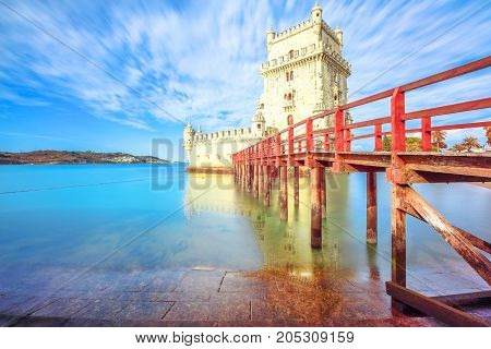 Scenic Belem Tower and wooden dock reflects with low tides on Tagus River.Torre de Belem is Unesco Heritage and symbol of Lisbon, in Belem District, and the most visited attraction in Lisbon, Portugal