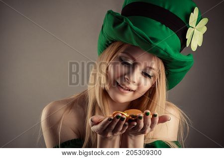 attractive leprechaun girl with coins in hands