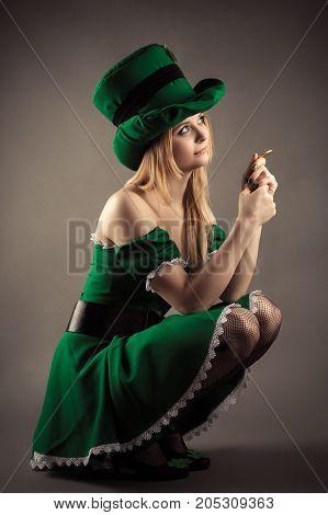 beautiful blond girl in leprechaun clothes sitting with a coin
