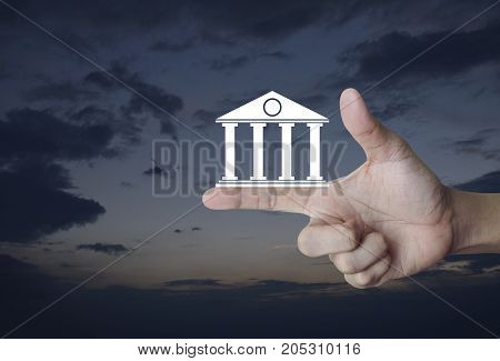 Bank icon on finger over sunset sky Business banking online concept