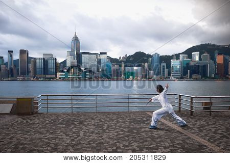 Beautiful view of Hong Kong skyline in the morining with people doing Tai Chi Hong Kong China