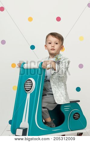 Boy On A Toy Motorcycle On A White Background