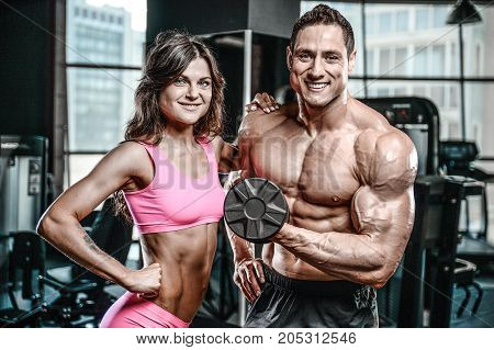 Handsome young muscular Caucasian man and woman working out training in the gym gaining weight pumping up muscles and poses fitness and bodybuilding concept