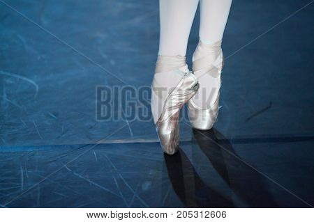 spectacle, dancing, equipment concept. two small aesthetic feet in beautiful pink pointe shoes of ballerina, dancing on the scratched floor of the theater stage