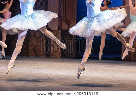 glory, entertainment, agility concept. slender but strong ankles and legs of two jumping ballerinas in snowy white tights and new creamy pointe shoes photographed in the movement