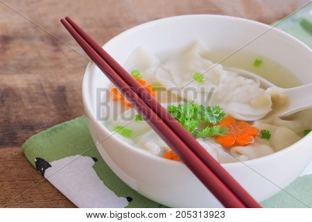 Homemade minced pork wonton soup in white bowl on napkin put on wood table. Delicious wonton in clear soup for breakfast or lunch or dinner. Wonton or dumpling is always popular Chinese food. Wonton or dumpling soup ready to served.