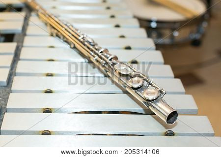 symphonic and brass band, percussion and wind instrument concept - beautiful closeup on western concert flute lies on beige bars of xylophone, orchestra, ensembles, jazz concerts, selective focus