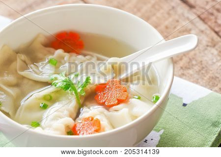 Close up minced pork wonton soup in white bowl on napkin put on wood table. Homemade delicious wonton in clear soup for breakfast or lunch or dinner.Wonton soup is always popular Chinese food. Wonton or dumpling soup ready to served.