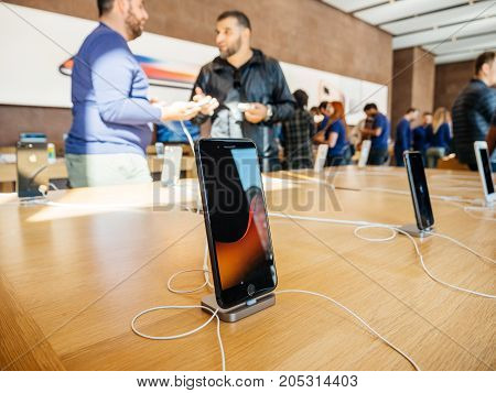 PARIS FRANCE - SEP 22 2017: New iPhone 8 and iPhone 8 Plus charging in docking station goes on sale today in Apple Store with middle East ethnicity customers holding admiring the phone