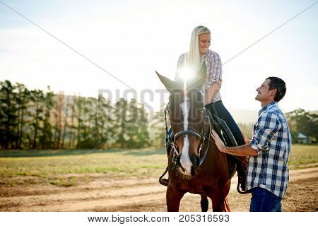 Smiling Woman Sitting On A Horse Talking With Her Husband