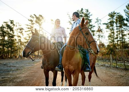 Smiling Couple Riding Along A Trail On Chestnut Horses