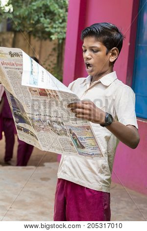 PONDICHERY PUDUCHERY INDIA - SEPTEMBER 04 2017. Young man reads newspaper in the school in front of the other children and teachers. Each monday morning he uses to read the newspaper for world news.