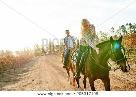 Young Woman Out Horseback Riding With Her Husband In Autumn