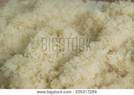 Hot sticky rice in a container on table in colse up