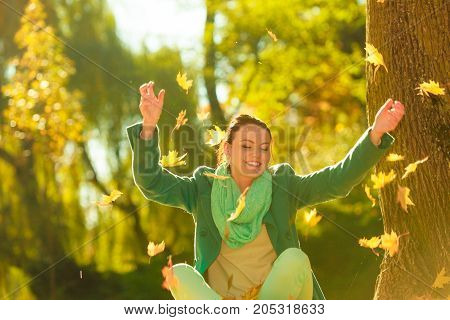 Happy woman throwing autumn leaves in park during beautiful sunny autumnal weather.