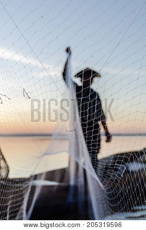 Asian fisherman on wooden boat casting a net for catching freshwater fish in nature river in the early morning before sunrise.Fishermen fishing in the morning light.