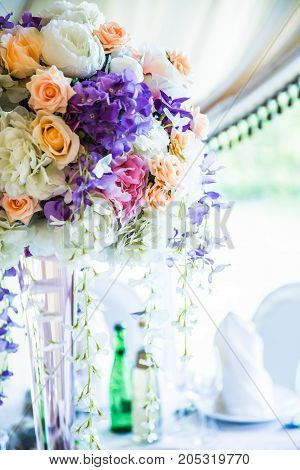 flowers bouquet in vase on the table in bright hall
