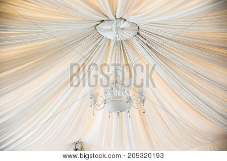 beautiful crystal chandelier in a white hal, with the cloth