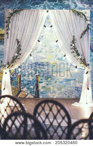Wedding white arch in studio with art background