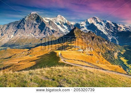 Fantastic alpine panorama with famous mountains peaks Jungfrau Monch Eiger North face and Mannlichen cable car station Grindelwald Bernese Oberland Switzerland Europe