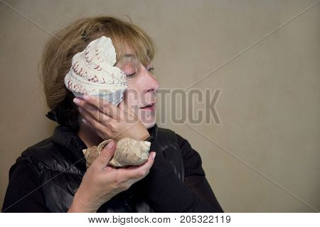 Woman holding a seashell and listening to the sounds out of it portrait studio shot