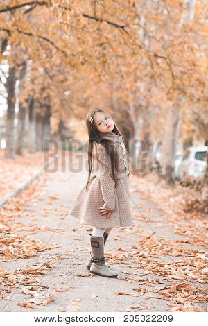 Stylish kid girl 4-5 year old wearing trendy winter jacket and boots standing in street aith fallen leaves. Looking at camera. Autumn season.