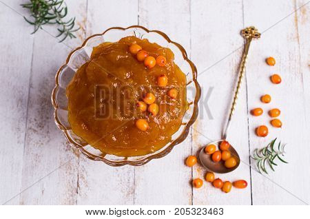 Sea buckthorn confiture in glass with berries and leaves. Selective focus.