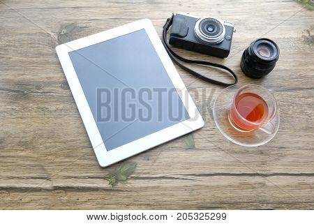 Workplace with office tools and gadgets. Cup of coffee on a table. Tablet, phone and camera to develop applications or other projects