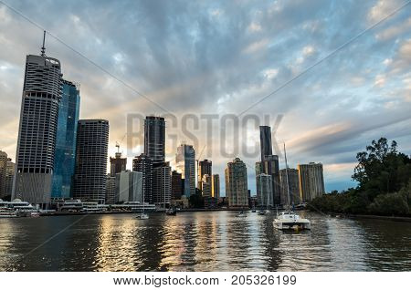 Brisbane, Australia - July 9. 2017: Brisbane city skyline and the Eagle Street Pier on the Brisbane River at sunset. Brisbane is the capital of Queensland state.