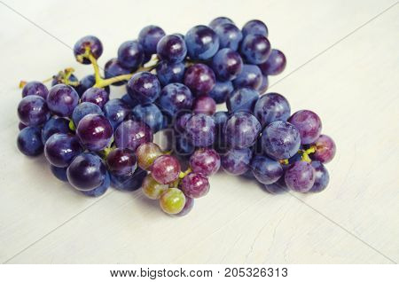 Dark blue grape isolated on white background. Pile of fresh ripe grapes.