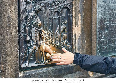 Prague, Czech Republic - September 27, 2014: Tourist is touching a bronze plaque of Saint John Nepomuk's dog part of the statue of St. John Nepomuk on Charles Bridge for good luck.