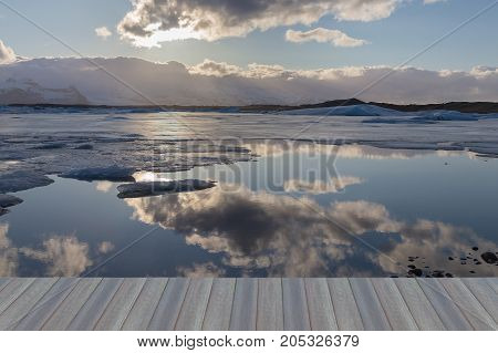 Opening wooden floor Reflection sky over winter season lagoon with sunset behind cloud Iceland natural landscape background