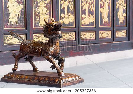 Bronze dradon statue in a buddhist monastery with a decorated wall in the background, Chengdu, China