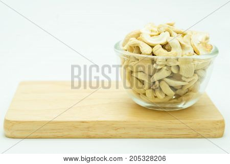 Cup of almond on glass cup over wooden board isolated