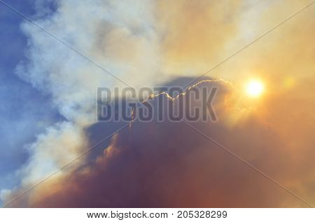 Bushfire smoke rising into the sky and blocking the sun. Natural disaster, danger and apocalypse concepts.