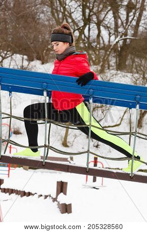Workout in public park. Woman wearing warm sportswear urban street training exercising outside during winter.