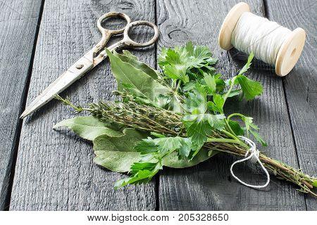 Bouquet garni. Classical french composition. Bay leaf parsley and thyme bound with culinary thread. Bunch of fresh aromatic herbs coil with threads scissors on dark wooden table
